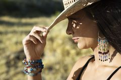 Young woman tipping a cowboy hat. Close-up profile of mid-adult Caucasian woman tipping straw cowboy hat Royalty Free Stock Photo