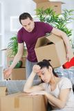 Young woman tired while unpacking boxes disapproving boyfriend stock images