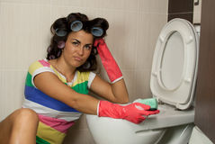 Spring Clean out. Young woman tired of washing toilet in the flat Stock Image