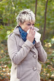 Young woman with tissue blowing her nose Royalty Free Stock Photography