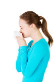 Young woman with tissue - sneezing. Royalty Free Stock Photography