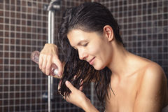 Young woman about to apply hair oil. To her newly washed hair standing in the bathroom in a towel dispensing into her hand from the bottle stock photo