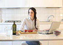 Young woman about to cook. Young beautiful woman looking at her laptop and about to cook in the kitchen Royalty Free Stock Photos
