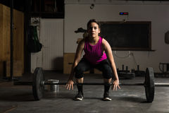 Young woman about to lift a barbell Royalty Free Stock Image