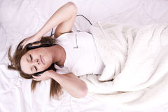 Young woman to stay in bed and listening music Stock Images