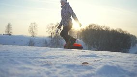 Young woman tobogganing running in the mountains through the sun in slow motion in winter have a good time. 1920x1080 stock video footage