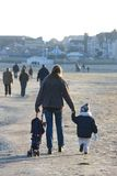 Young Woman and Toddler Son on Beach in Winter Stock Photography