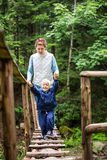 Young woman and toddler son walking along pendant bridge Stock Image