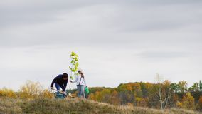 Young woman, together with her daughter, plant a tree. Woman, together with her daughter, plant a tree. Against the background of autumn landscape stock video footage