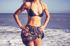 Young woman with toned abs standing on the beach Royalty Free Stock Images