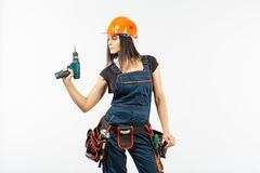 Young woman with toolbelt using driil and some power tools for her work at home. Girl working at flat remodeling. Building, repair. Young woman with toolbelt Royalty Free Stock Photo