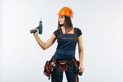 Young woman with toolbelt using driil and some power tools for her work at home. Girl working at flat remodeling. Building, repair. Young woman with toolbelt Royalty Free Stock Photos