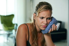 Young woman with toothache holding ice bag on cheek Stock Photos