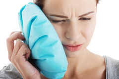 Young woman with toothache and ice bag. Royalty Free Stock Photos