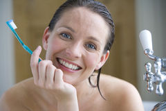 Young woman with toothbrush in bath, chin in hand, smiling, portrait, close-up Stock Photo