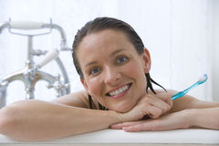 Young woman with toothbrush in bath, smiling, portrait, close-up. Young women with toothbrush in bath, smiling, portrait, close-up Royalty Free Stock Photos