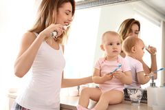 Young woman with toothbrush and daughter near mirror. Young women with toothbrush and daughter near mirror in bathroom royalty free stock image