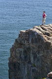 Young woman at the top of a cliff overlooking the ocean. A young woman in a pink top triumphantly stands at the top of a rocky cliff while looking out over the Stock Photography