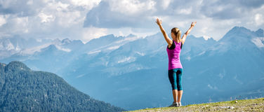 Young woman on top of the mountain. With the arms raised Stock Photo