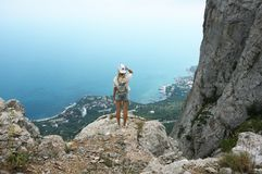 Young woman on top of mountain. Young woman standing on top of mountain against sea at cloudy weather. Back view Royalty Free Stock Photo