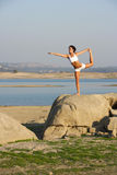 A young woman on top of a rock doing yoga Royalty Free Stock Images