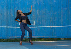 Young woman in top, shirt and leggins on high heels with modern makeup and hair dancing against blue painted wooden wall Stock Photo
