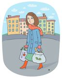 Young woman with tote bags goes from the city market to home. A young woman holds two tote bags with food from the market in the old city