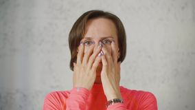 Young woman touch eyes with fingers then open and close eyes. Close up woman portrait. Female in red rose turtleneck looking to camera stock video footage