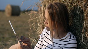 Young woman with touch pad in the countryside. Dolly shot of a young woman using tablet PC in the countryside. She sitting by the hay roll in the field stock footage