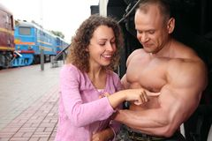 Young woman  touches by finger  biceps of athlete Royalty Free Stock Photography