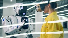 Young woman touches robot`s hand while wearing modern VR glasses. stock footage