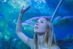 Young woman touches a stingray fish in an oceanarium tunnel.  royalty free stock photography