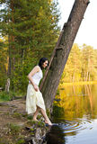Young Woman touches water in the forest lake Royalty Free Stock Images