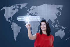 Young woman touching a button of start into 2014 Stock Photo