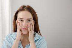 Young woman touching cheeks self-massage Stock Image