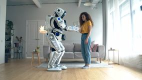 Young woman is touching a cyborg in a living room stock footage