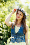 Young woman touching flower wreath on her head. Beautiful summer portrait Royalty Free Stock Image