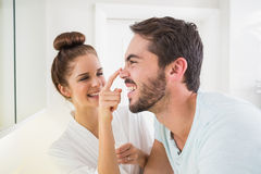 Young woman touching her boyfriends nose Royalty Free Stock Photos