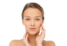 Young woman touching her face Stock Images