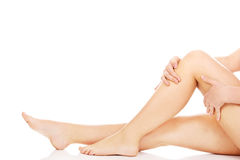 Young woman touching her legs Stock Photo
