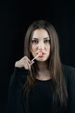 Young woman touching a lollipop on her juicy big lips Royalty Free Stock Photos