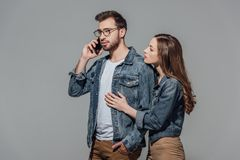 Young woman touching and looking at stylish man in eyeglasses talking on smartphone. Young women touching and looking at stylish men in eyeglasses talking on Royalty Free Stock Image