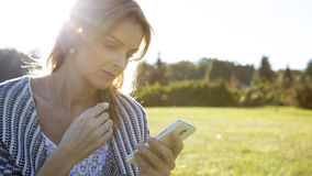 Young woman touching smartphone. Young woman touching cell phone Stock Photo