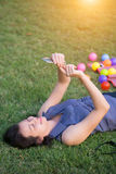 Young woman touching smartphone on green grass Royalty Free Stock Photos