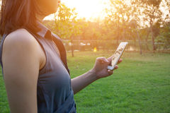 Young woman touching smartphone on green grass Stock Photo