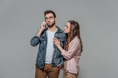 Young woman touching stylish man in eyeglasses talking on smartphone. Young women touching stylish men in eyeglasses talking on smartphone isolated on grey Stock Image