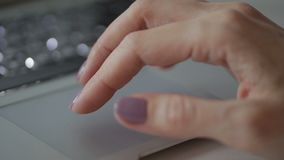 Young woman is touching touchpad of laptop with fingers at table indoors. Female user uses silvery device while sitting at desk in room. She touches sensory stock video footage