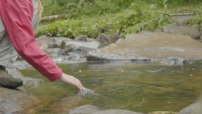 Young woman touching the water of the river in the forest. Young tourist touches the river hand Stock Photo