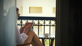 Young woman with touchpad on hotel balcony stock video