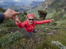 Young woman tourist in alpine zone in summer, man helping her to Royalty Free Stock Photos